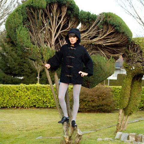 Ung vuxen kvinna halvt uppklättrad i träd